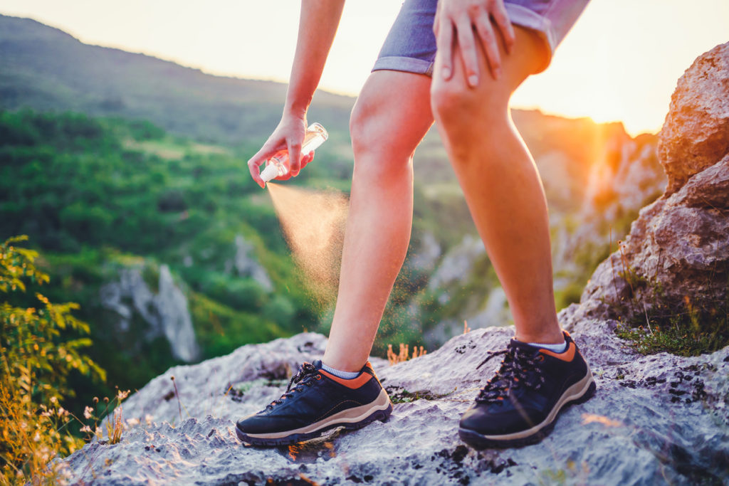 Woman spraying mosquito repellant while hiking