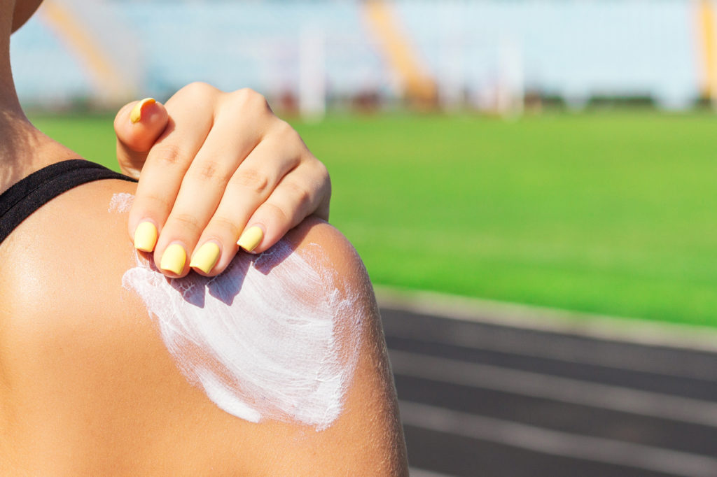 Woman applying sunscreen at sports event