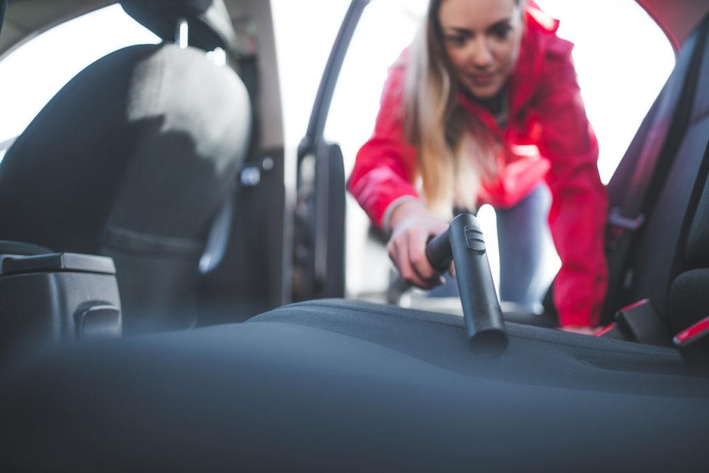 Woman vacuuming her car upholstery